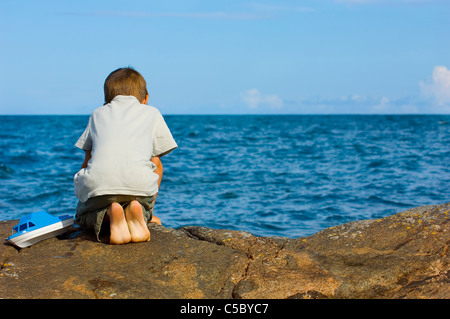 Rear view of a boy sitting on rock overlooking the blue sea - Stock Image