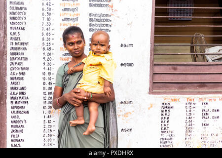 Woman holding a baby in the bus station at Kumily, Thekkady, Kerala, India. She is standing in front of a list of destinations. - Stock Image