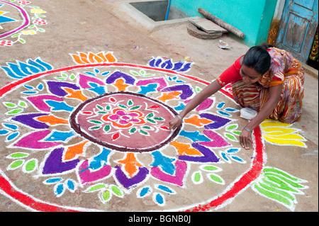 Indian woman making a Rangoli festival design in an Indian street at the hindu festival of Sankranthi. Puttaparthi, - Stock Image