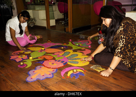 Indian girls design a Rangoli with traditional colors to welcome deities ahead of the Hindu festival of Diwali. - Stock Image