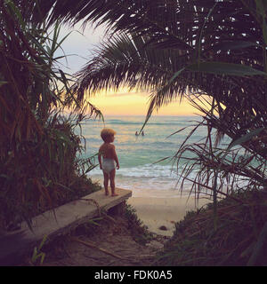 Boy standing on wall looking at beach - Stock Image