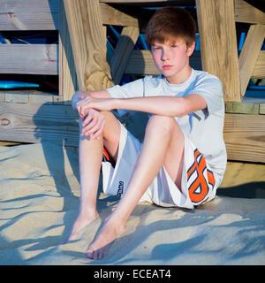 Boy sitting on beach leaning against boardwalk - Stock Image