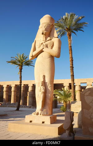 Karnak, Egypt - Statue of Pharaoh Ramses II with Queen Nefertari in the Great Courtyard, Amun-Re Temple - Stock Image