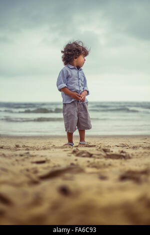 Boy standing on the beach - Stock Image