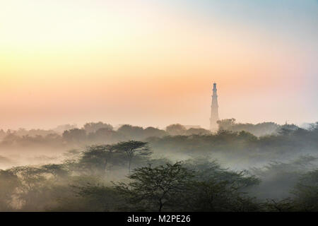 An early morning winter sunrise with fine layer of mist at the most iconic Qutub Minar in the capital city of New - Stock Image