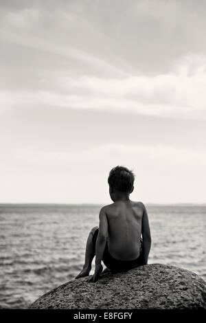 Boy sitting on rock by the sea - Stock Image