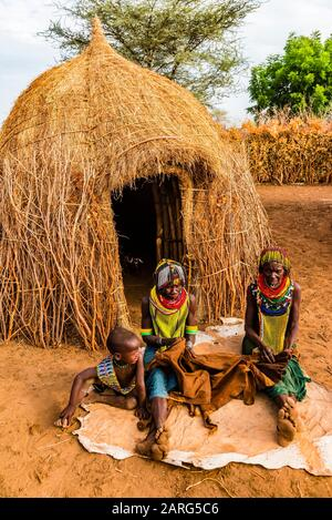 Nyangatom tribe women and children sit in front of their hut in their village, Omo Valley, Ethiopia. - Stock Image