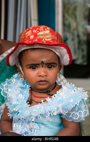 India, Kerala, Munnar, young female child dressed in frilly blue dress and red sun hat - Stock Image