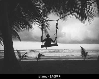 Silhouette of boy sitting on a swing on the beach - Stock Image