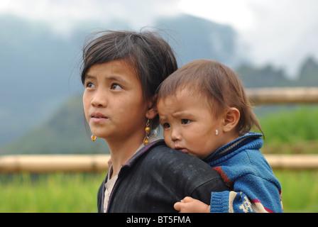 Tribal Black Dao girl carrying baby brother near Sapa, Vietnam - Stock Image