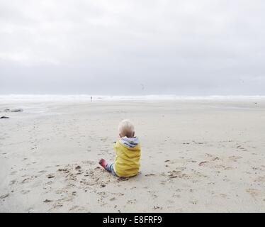 Rear view of boy sitting on the beach in a raincoat - Stock Image