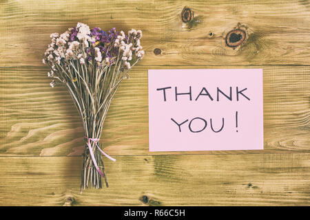 Beautiful bouquet of flowers and text thank you on wooden table. - Stock Image