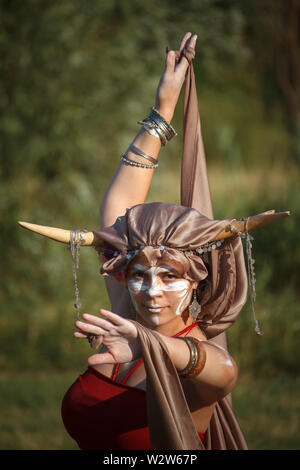 Kharkiv, Ukraine - July 06, 2019: Young woman dancer with painted face and horns on her head is standing in the dance pose and looking at the camera - Stock Image