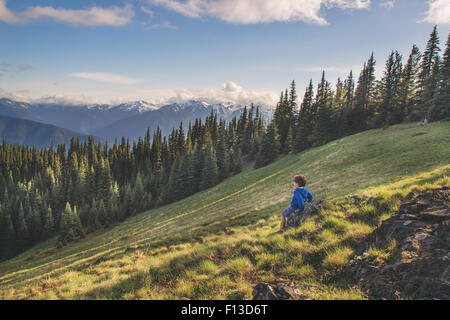 Boy sitting on a rock on a mountain - Stock Image
