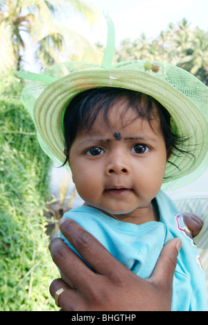 Cute Baby in the hands of her father looking on the Lens Sharply .A Scene from Kerala,India - Stock Image