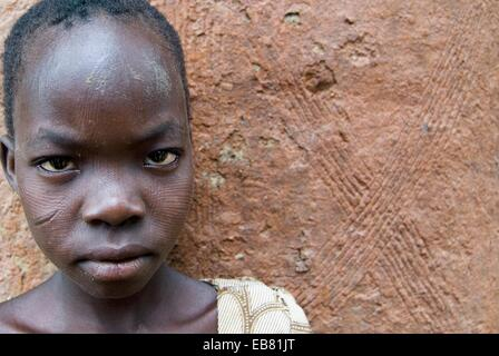 A young Somba  Betamaribe  girl standing by her home in small village in Northern Benin  Linear scars can be seen - Stock Image