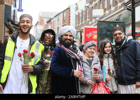 Rochdale, UK. 9th November, 2019. Hundreds take to the streets in a  procession for Mawlid al-nabi, the observance of the birthday of Islamic Prophet Muhammad. The procession passed though the Deeplish and Milkstone areas before reaching the town centre. Roses were handed out in the town centre to passers shoppers to celebrate both Malid and  in remembrance of those who gave their lives in Wars.  Rochdale, Lancashire, UK. Credit: Barbara Cook/Alamy Live News - Stock Image