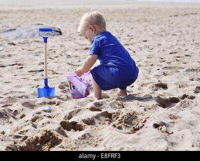 Boy playing in the sand on the beach - Stock Image