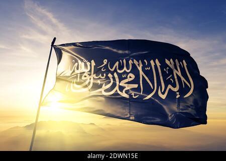 Prophet Muhammad flag waving on the top sunrise mist fog - Stock Image