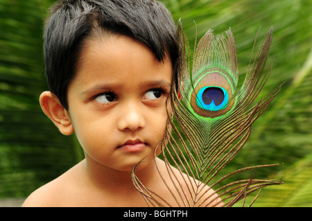 Baby and Peacock feather - Stock Image