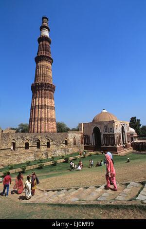 qutub minar delhi india indian tourist traditional dress in foreground sari salwar - Stock Image