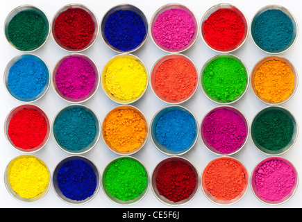 Coloured Indian powder in metal bowls used for making rangoli designs. White Background - Stock Image
