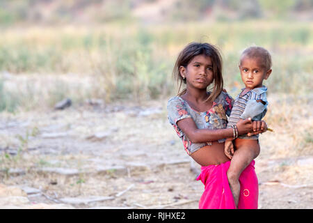 A young girl from the Bhil tribe holds a younger male in rural Rajasthan near Bhainsrorgargh, India. - Stock Image