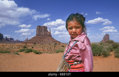 A young Navajo girl, dressed in traditional velveteen clothing and silver and turquoise jewelry, near her mother's hogan in Monument Valley Navajo Tri - Stock Image