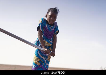 Joyful African ethnicity Young Woman Carrying pure Water in Bamako - Stock Image