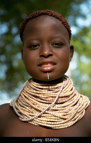 Young girl with henna in hair and wearing beads and nail, Omo camp, Murulle, Ethiopia, Africa - Stock Image