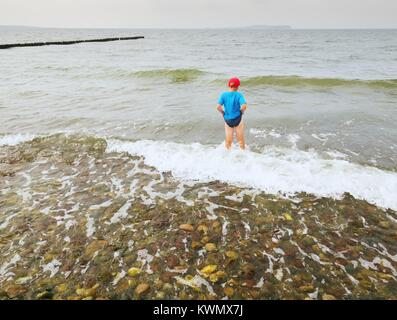 Boy in blue black sporty clothes stay in cold foamy sea. Blond hair kid in waves at stony beach. Windy day, cloudy - Stock Image