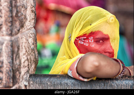 Young beautiful Indian girl waiting for the bus in traditional colored clothes, sari - Stock Image