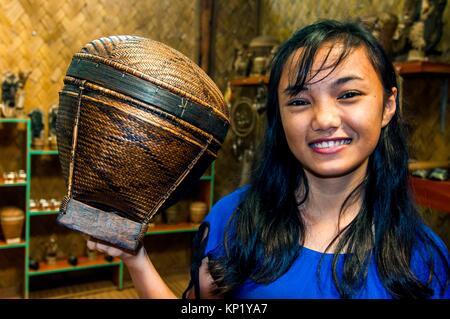 Tingkop basket held by young woman at Tagbanwa tribal village souvenir shop, Butterfly Garden, Puerto Princesa, - Stock Image
