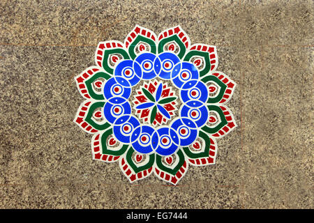 Printed, colorful, geometrical pattern of rangoli stuck on mosaic tiled floor - Stock Image