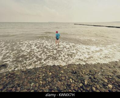 Blond hair boy stay in cold sea tide. Kid on stony beach with foamy waves. Windy day, cloudy blue sky on seascape - Stock Image
