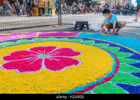 Boy adding rice to large mandala Rangoli floor decoration India Live Street Festival Celebration, Vancouver, British - Stock Image