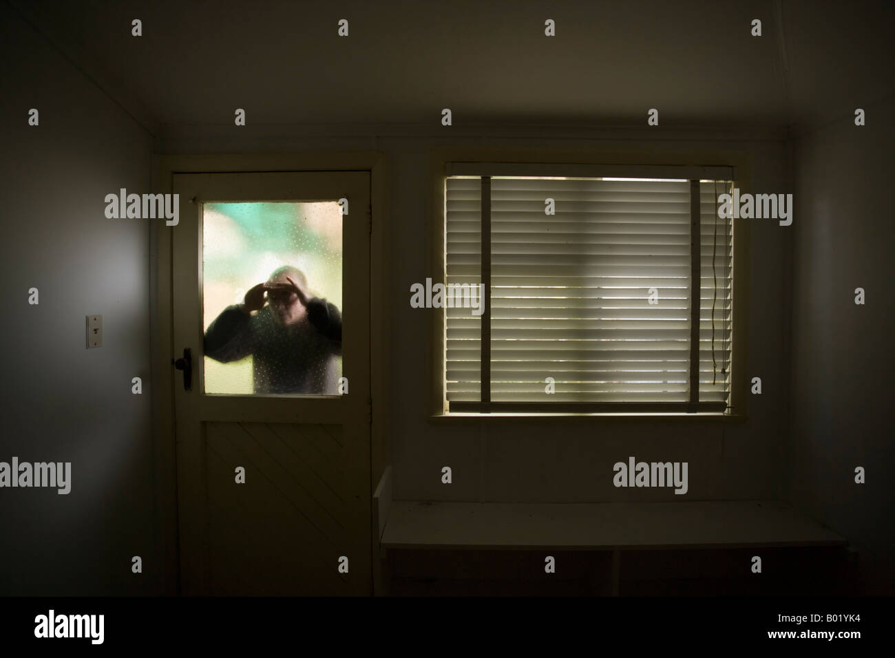 man-looks-into-room-through-frosted-glas