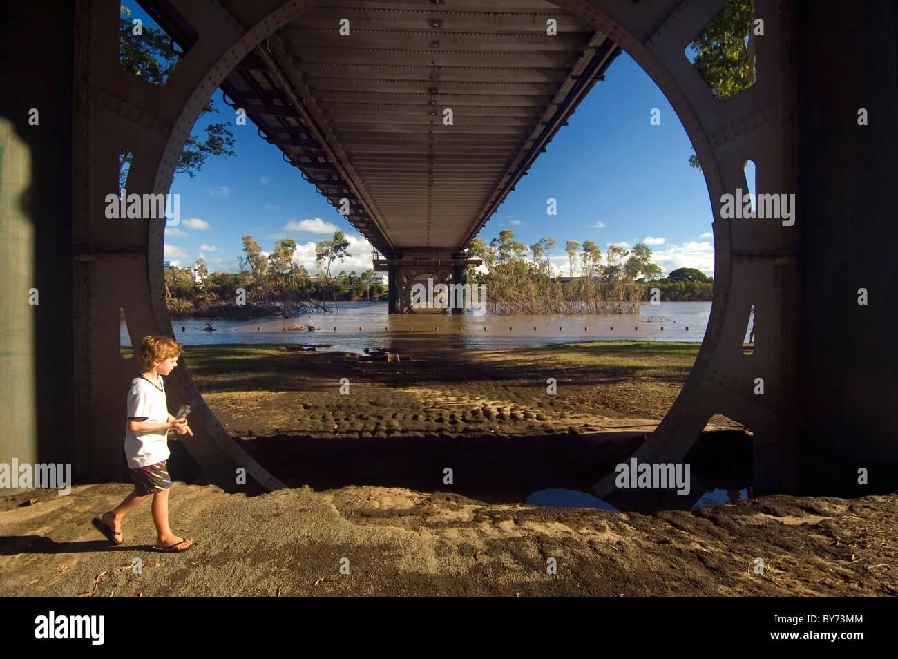Boy looking at flood damage underneath the Burnett River Bridge, Bundaberg, Queensland, Australia, January 2011. Stock Photo