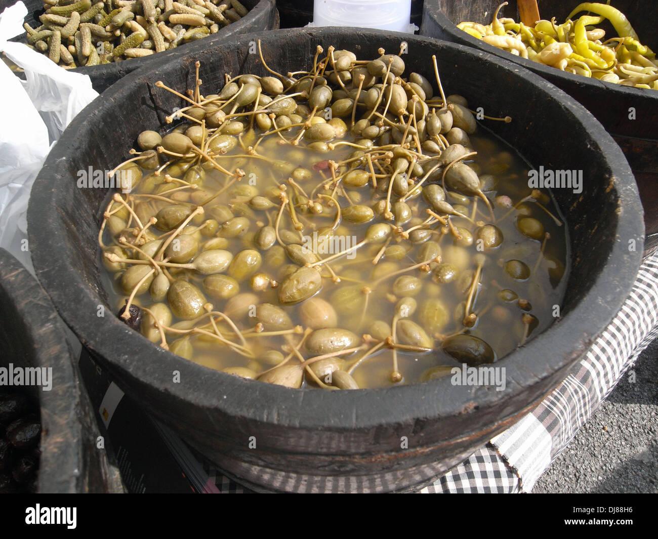 Caperberries preserved in vinegar, in local Catalan market in Barcelona, Spain Stock Photo