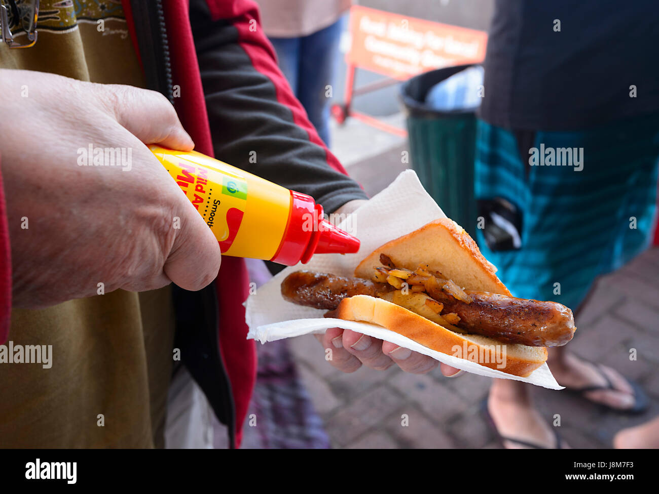 person-pouring-mustard-on-a-bunnings-war