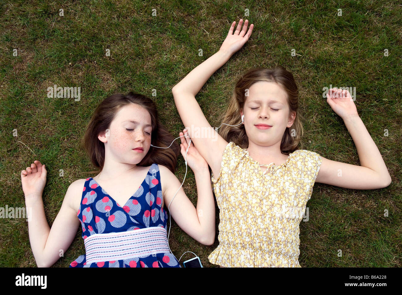 girls-lying-on-grass-with-earphones-B6A2