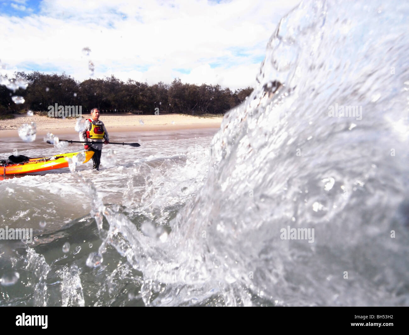 Sea kayaker entering heavy surf from beach, Noosa, Sunshine Coast, Queensland, Australia. MR Stock Photo