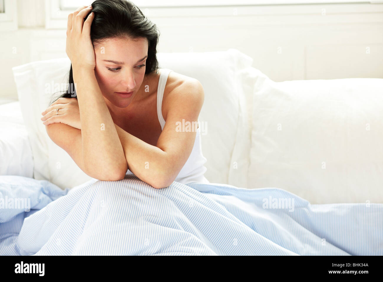 woman-sat-alone-in-bed-BHK34A.jpg
