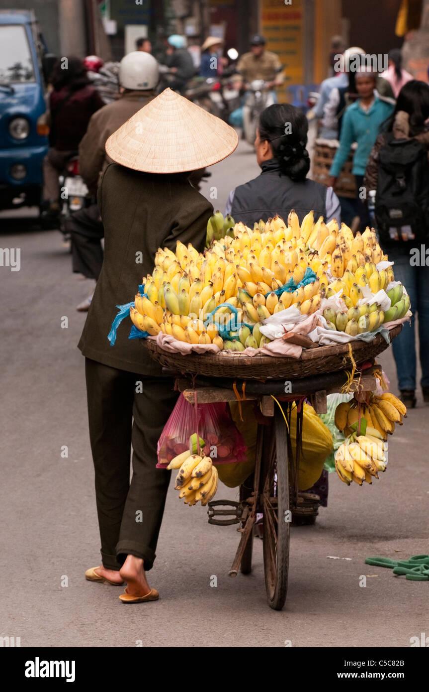 Street hawker carrying bananas, Ma May St, Hanoi Old Quarter, Vietnam Stock Photo