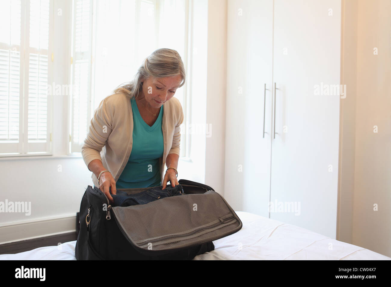 older-woman-packing-a-suitcase-CW04X7.jp