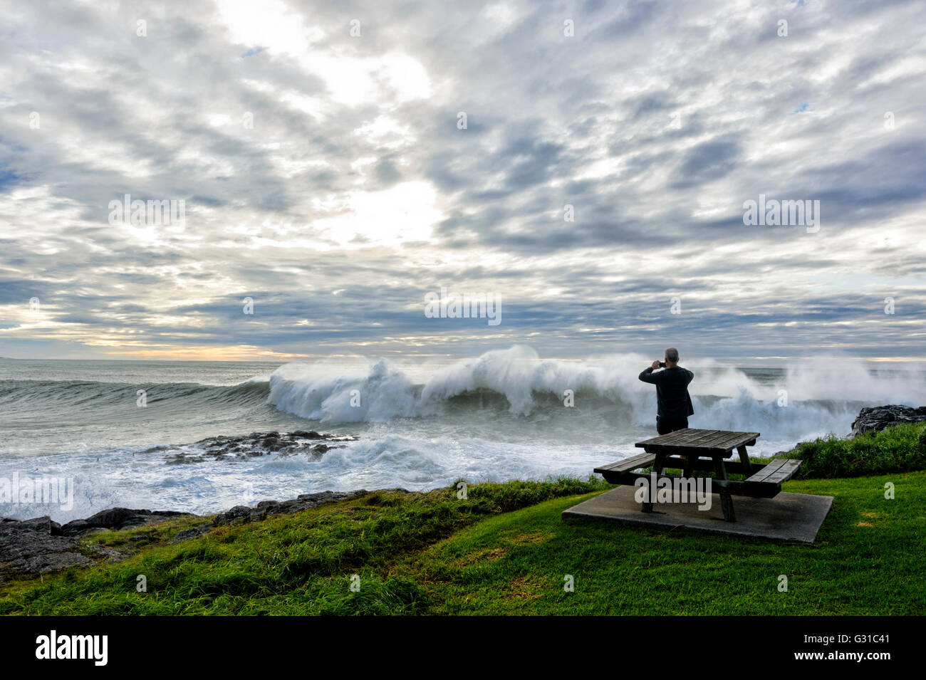man-taking-pictures-of-stormy-seas-at-su