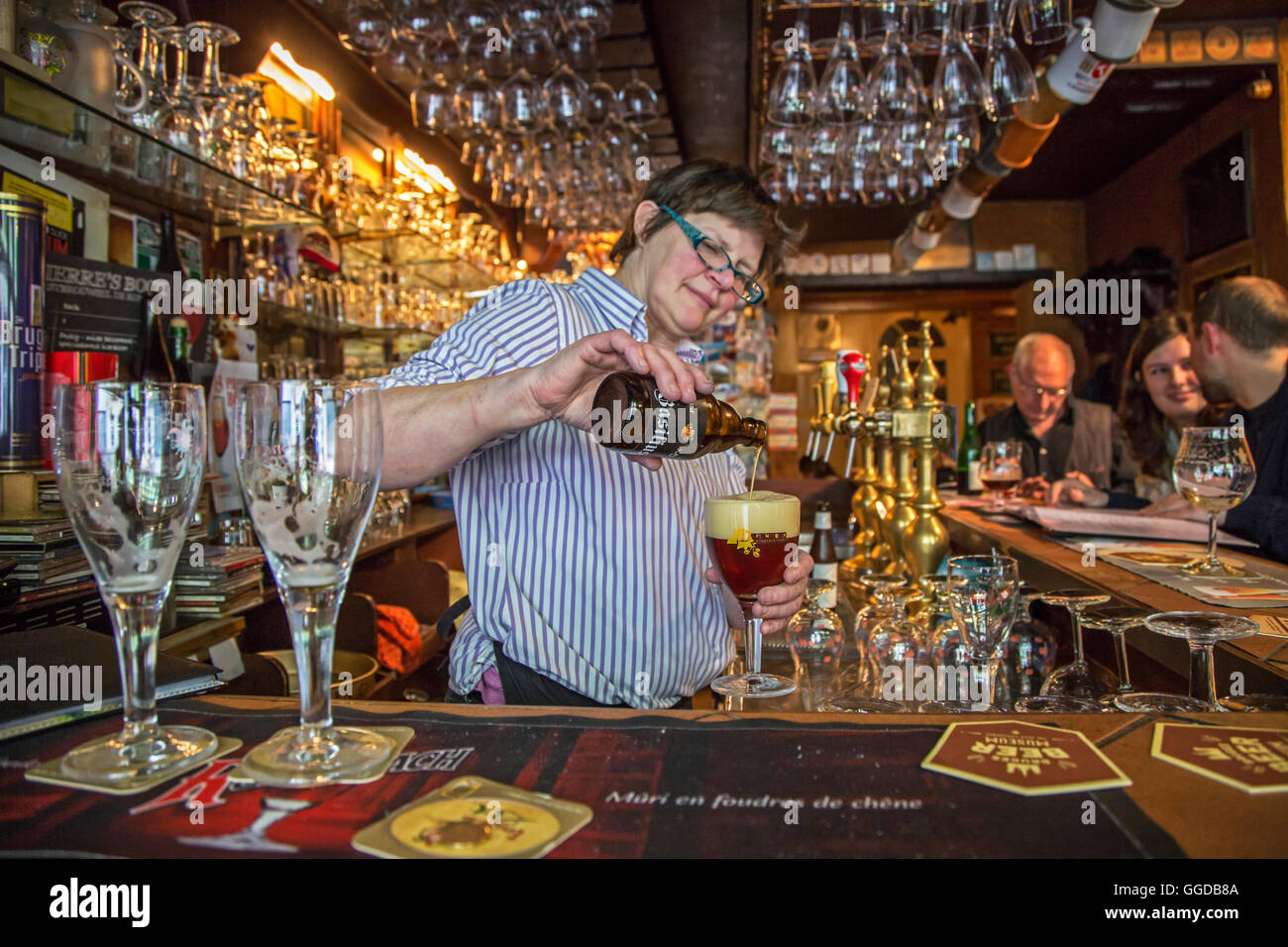 bartender-pouring-belgian-beer-in-glass-