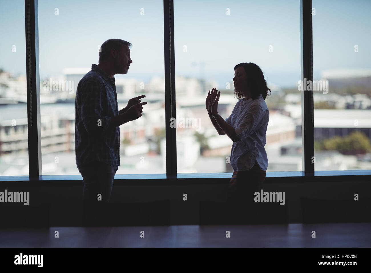 couple-arguing-near-the-window-in-office