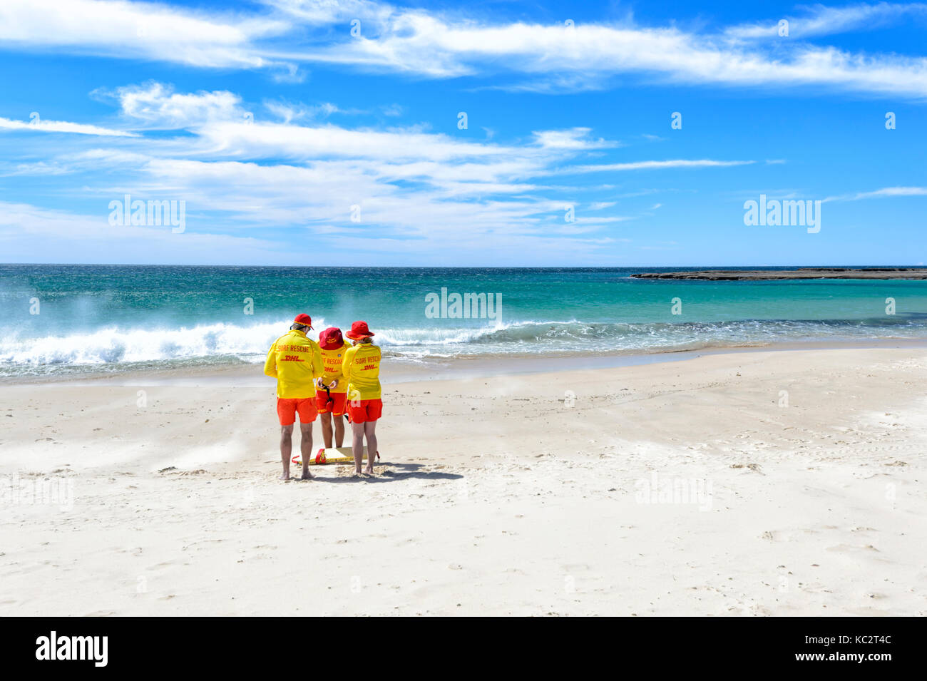three-lifeguards-standing-on-the-beach-a