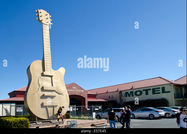 Tourists posing in front of the Big Golden Guitar, Tamworth Australia - Stock Image